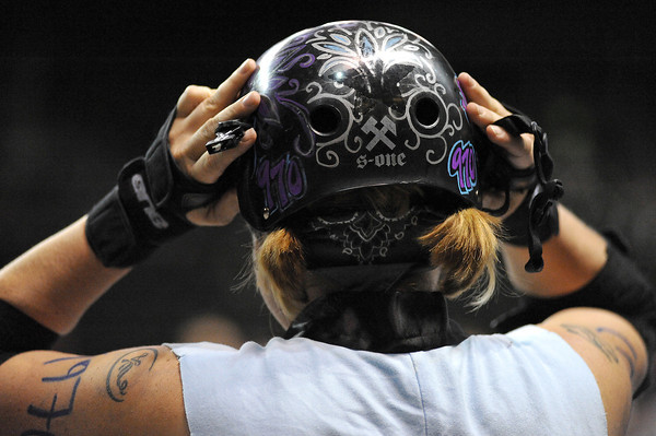 """Kris """"Siquin Destroy"""" Reed from the Fort Collins' Kung Fu Donnas puts on her helmet moments before the start of their rollar derby match Sunday against Greeley's Slaughterhouse Derby Girls at the Budweiser Event Center."""