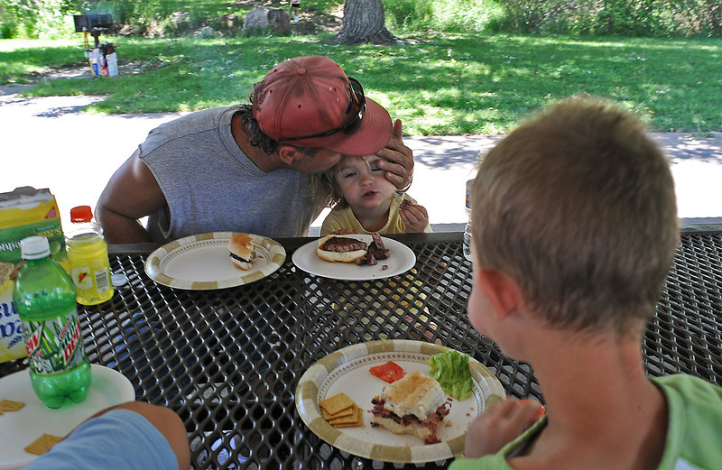 Jay Hiller shows his affection for his daughter, Jessica, 3, as they and Jessica's brother, Jordan, 6, eat during a barbeque meeting of the Northern Colorado Parents Without Partners group at Rolland Moore Park in Fort Collins. The group of single parents regularly meets to offer support for each other and to allow their kids to be with other kids going through similar situations at home.