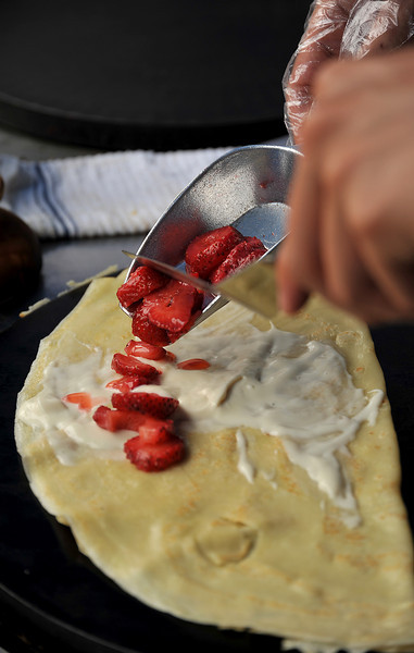 Ben Blackman carefully adds strawberries onto a sweet crepe Saturday while cooking for a customer during Loveland's annual Summerfest near downtown.