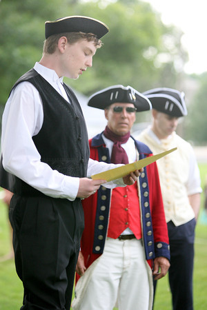 B.J Evans, 14, a member of the Loveland 912 project dressed in clothing similar to that from 1776, reads a portion of the Declaration of Independence to people gathered at North Lake Park on Saturday. Dae Cook, center and Brian Evans, right, are in the background.