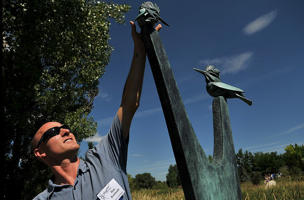"""Artist Don Rambadt discusses his recent sculpture, """"Requiem for a Fallen Tree"""" with on-lookers Saturday morning at the Sculpture Dedication Ceremony which was held at Benson Sculpture Garden in Loveland. Rambadt, who flew in all the way from Trevor Wisconsin, says of the event, """"it's an honor to be included amongst these other artists."""""""