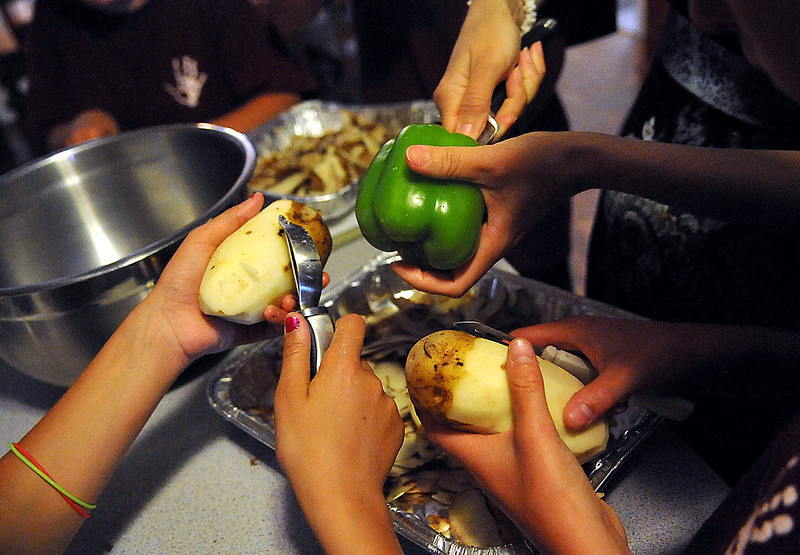 "Anastasiya ""Nastia"" Pyzhuk, 11, left, works with Maryna Mygovych,12, right and Yulia ""Julia"" Sergienko, top center, to prepare vegetables for an authentic Ukrainian meal Sunday at the Stoesz household in Berthoud. The children came from Novapetrovski, Ukraine to attend a Cultural Exchange Camp through the Ukraine Orphan Outreach program."