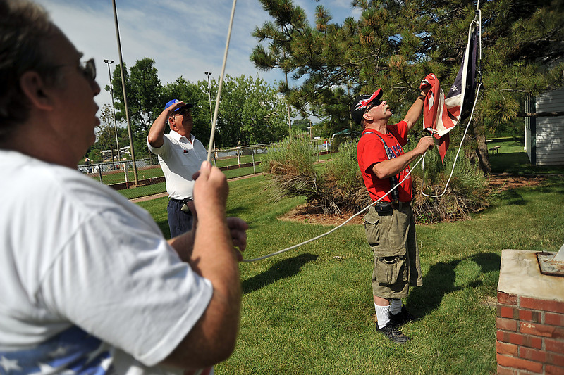 Tom Buchanan, far right, raises the American flag with Bob Konzem, center, and Dick Wood, far left, on Saturday morning at North Lake Park in Loveland. Buchanan and Konzem, both war veterans, were asked to raise the flag when the boy scout troop that was orinigally scheduled couldn't make it.