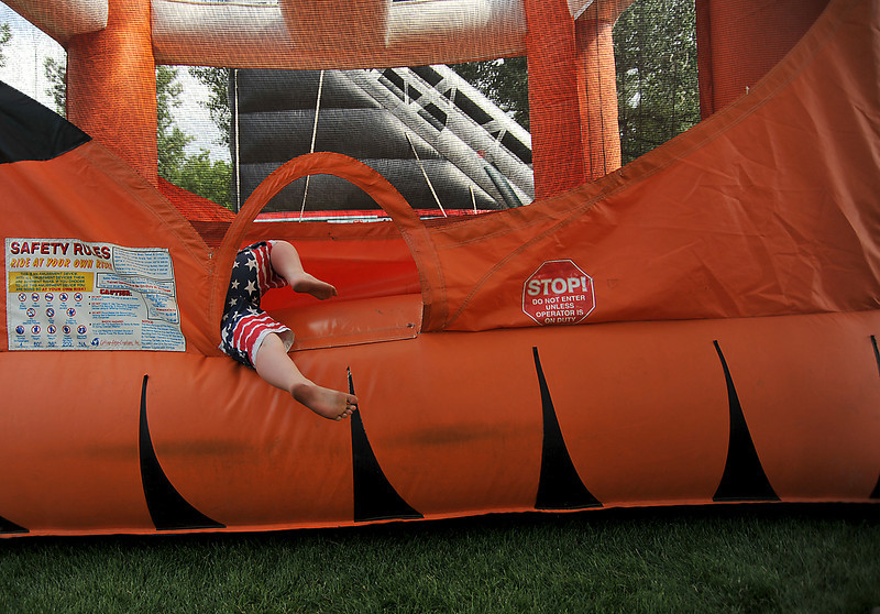 Zane Grubb, 8, climbs into an inflatable bouncer Saturday during Loveland's annual Summerfest. The event offered everything from food to rides, to live music and it attracted a crowd despite rising temperatures.