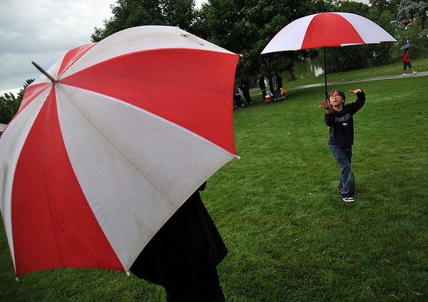 "Brian Adams, 8, skillfully balances his umbrella on his hand while waiting in the rain Saturday evening for the fireworks show at North Lake Park in Loveland. ""Rain can't keep us away!"" said his father Brad Adams."