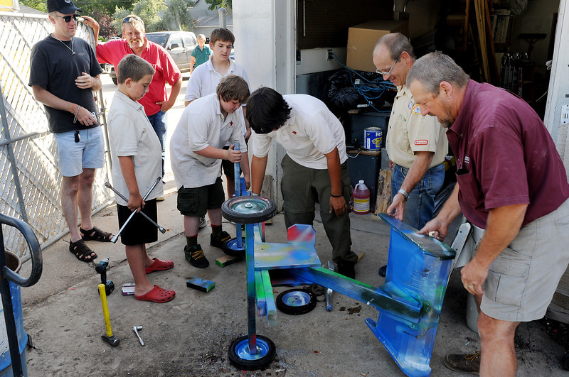 Boy Scout Troop 1051 rushes to assemble a soap box racer Tuesday evening in the pits at Red Line Heating and Cooling in downtown Loveland for a soap box derby west of town later in the evening. From left, are Dave Brown, Clayton McCall, 11, Steve Moritz, holding onto gate, Michael Moritz, 11, Ben Brown, 15, back, Vance Stenson, 15, Craig Keeton, and Kim Stenson.