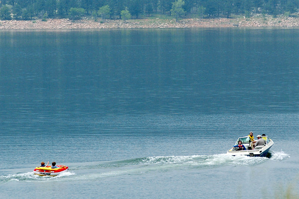 Brad Weaver, 10, left, gives a thumbs-up from an inflatable tube while he and Michael Sheinberg, 14, are towed behind a boat on Tuesday afternoon at Carter Lake.