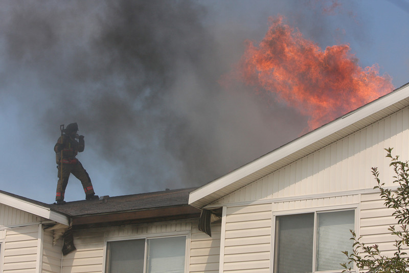 A firefighter stands on the top of a fourplex at the 600 block of Eagle Drive while flames burst through the roof Friday in Loveland.