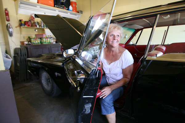 Cindy Wilson, widow of the former racecar driver Fritz Wilson, sits in a 1962 Plymouth Fury during an estate auction of Wilson's house, cars and tools.  The Fury was the last car that Wilson had finished before he died in 2007.