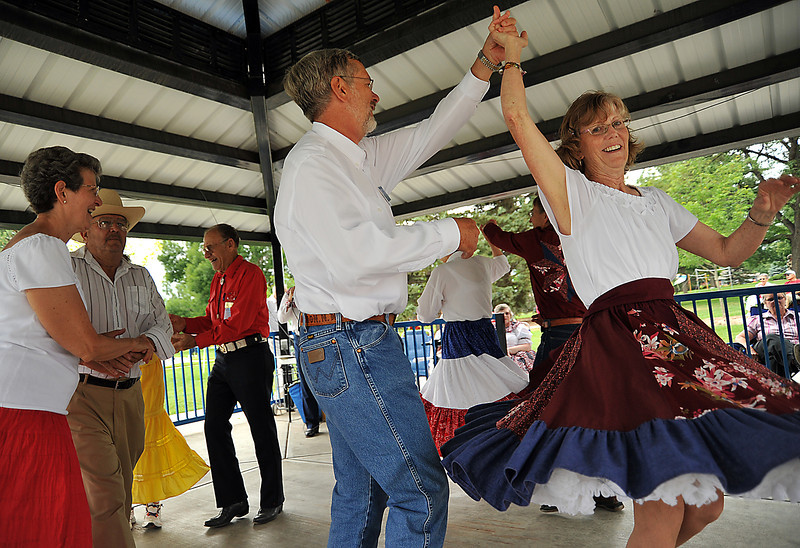 "Dolores Daniels is spun by Nels Broste as they square dance in North Lake Park Saturday during the Independence Day festivities in Loveland. Both dancers have been square dancing for years, and many in the group say they do it for the social aspect citing the square dancing motto, ""square dancing is friendship set to music."""