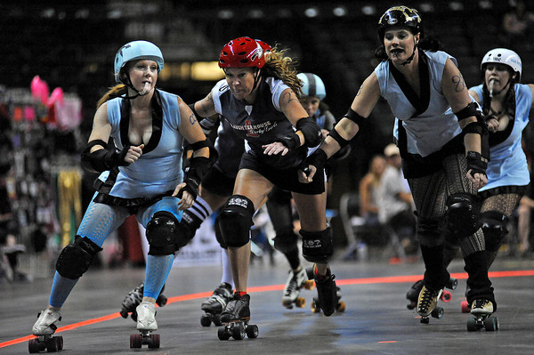 """Jerica """"Urrk'n Jerk'n As Booty Block 'Ya"""" Trevena, left, skates past TNT Dynomite from the Greeley Slaughter House Derby Girls, center, and Tara """"Yoshi Twisted"""" Cary, right, from her own team, the Fort Collins' Kung Fu Donnas, Sunday during their rollar derby match at the Budweiser Event Center."""