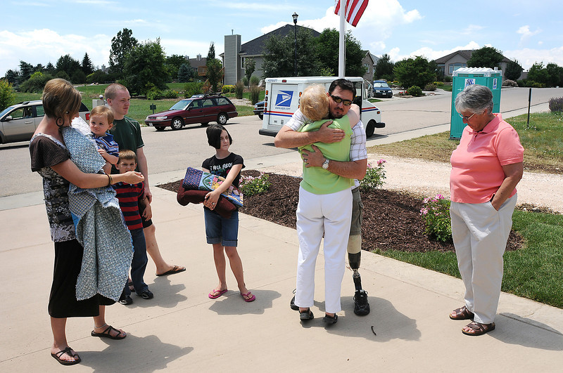 Disabled Iraq War veteran John Jones hugs Ann Eatman of Project Hero Quilts after she and Jean Belt, right, presented Jones and his family with quilts on Thursday at their new home in Fort Collins. Also visible, from left, is Jones' wife Amber, holds Wyatt, 1, Keegan, 8, John Jones' brother, Joshua Jones, and Jade, 11,