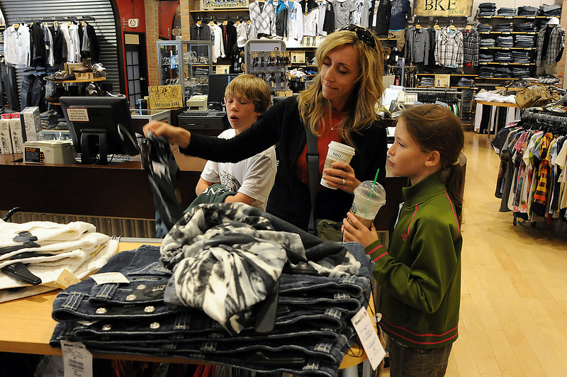 Tonya Yoder shops for back-to-school clothes for her son Roman, 11, left, and daughter Paris, 10, on Thursday at Buckle at the Promenade Shops. The store has remained busy despite economic woes.