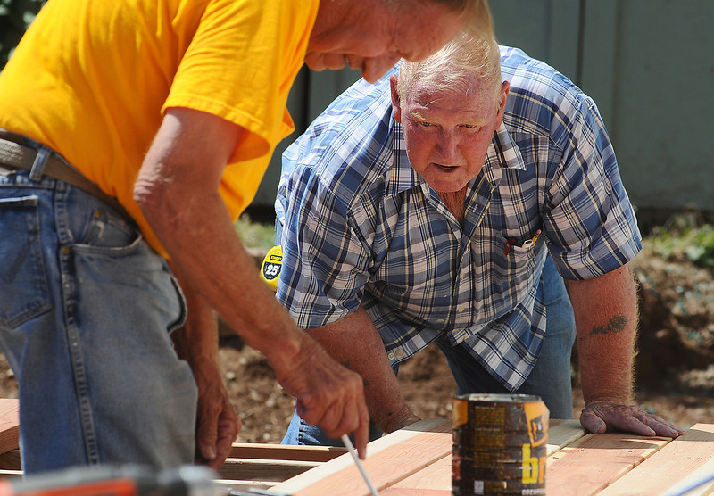 Jerry McCollum, 69, right, helps his friend Diz Disner with a deck at Disner's and his wife, Kay's house near Carter Lake on Sunday. Despite a recent knee surgery and several heart attacks, McCollum helps those in need by using the skills he learned as a builder.