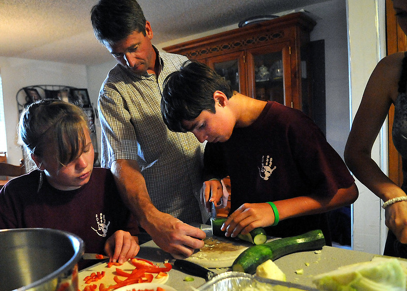 "Clarke Stoesz, center, helps Dmytro ""Dima"" Galenko, 14, chop vegetables while Olga Furtatenko, left, and Yulia ""Julia"" Sergienko, right, help Sunday at the Stoesz household in Berthoud. The Stoesz family was the second of two to host seven children from an orphanage in Novapetrovski, Ukraine for three weeks this summer through the Ukraine Orphan Outreach. The program, called the Cultural Exchange Camp, held a fundraiser where they served an authentic Ukrainian meal and held a silent auction to raise money for next year's camp."