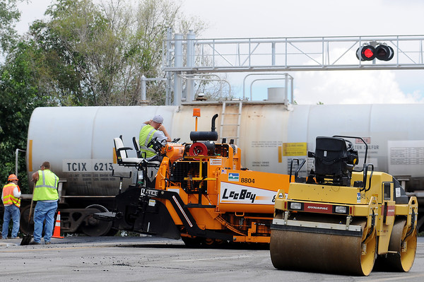 A train rolls by as City of Loveland crews pave 29th street where it abuts the railroad tracks on Monday afternoon.