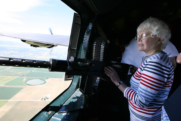 "Marian Lilker, a LaPorte resident, looks out the window of the ""Witchcraft,"" a B-24 bomber while holding onto a .50 caliber machine gun during a flight from the Rocky Mountain Metropolitan Airport in Broomfield to the Fort Collins-Loveland Municpal Airport on Friday. Lilker's deceased husband,  Ralph Morrow, was a B-24 pilot in World War II."