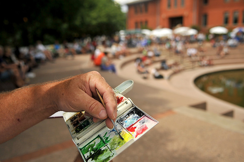 Kim Stenson dips his brush into watercolor paint Sunday while drawing a scene of people at Loveland's annual SummerFest. Stenson, who was also volunteering at the event, had already done two paintings during the festival.