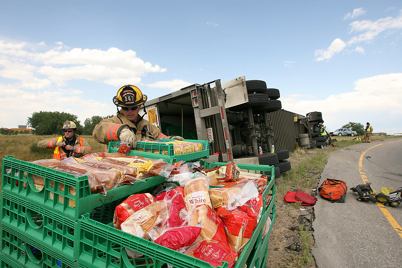 Loveland Fire and Rescue Lt. Mark Lyons, right, unloads bread off of a Safeway delivery truck that overturned on the Interstate 25 off-ramp to westbound U.S. 34 Thursday in Loveland as Battalion Chief Jeff Genger works the scene. The driver suffered a laceration on the left side of his head.