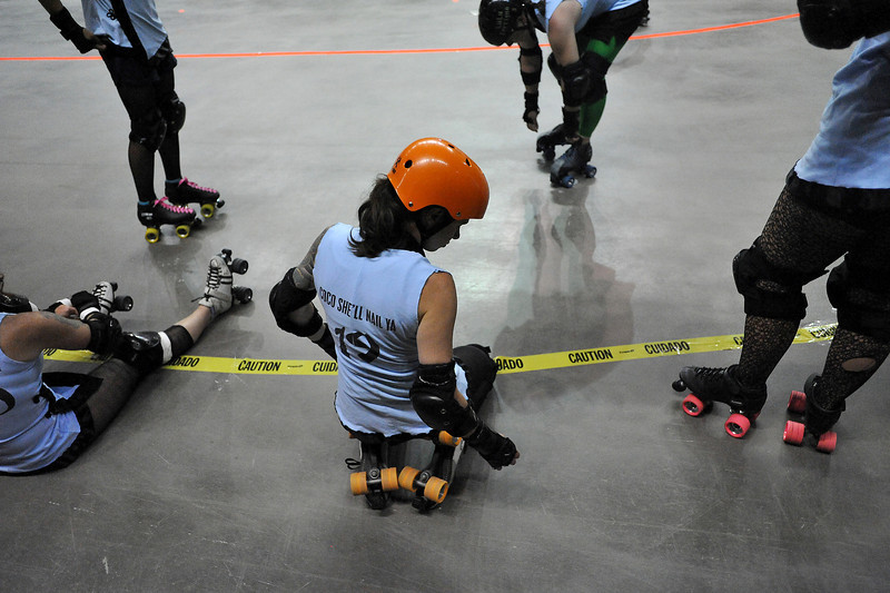 "Lesley ""Coco She'll Nail Ya"" Brandt takes a moment to stretch with her teammates from the Kung Fu Donnas before their rollar derby match Sunday at the Budweiser Event Center against Slaughterhouse Derby Girls."
