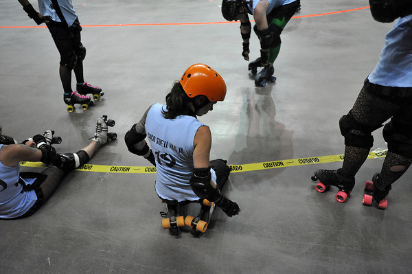 """Lesley """"Coco She'll Nail Ya"""" Brandt takes a moment to stretch with her teammates from the Kung Fu Donnas before their rollar derby match Sunday at the Budweiser Event Center against Slaughterhouse Derby Girls."""
