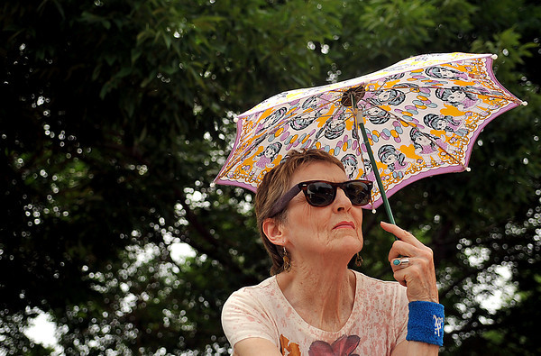 """Edi Echevarria shades herself from the sun while watching live music Sunday at SummerFest near downtown Loveland. """"I'm here for the live music, and there's plenty of it!"""" says Echevarria of the annual festival."""