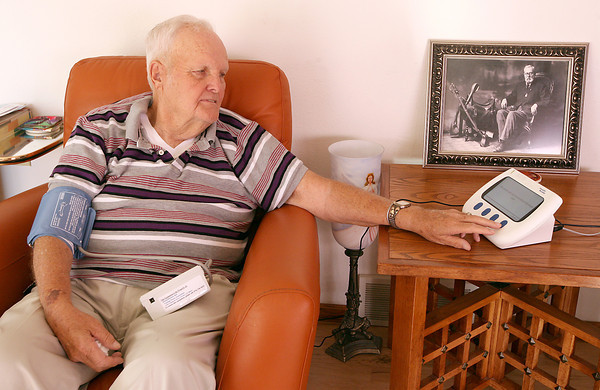 Tom Johnston, 75, checks his blood pressure using the Health Buddy, a device that checks a patients blood pressure and weight daily and sends the information to his doctor, Wednesday, July 1, at his home near Windsor.  Johnston had a quadruple bypass in March and his nurse is using the Health Buddy to monitor any sudden changes in his weight or blood pressure.