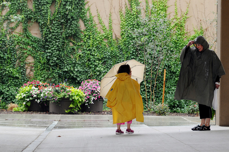 Esther Noble, 5, and her mother Aimee look for a spot to have a late lunch at Lincoln Place in downtown Loveland during a mid-afternoon rainstorm on Wednesday.