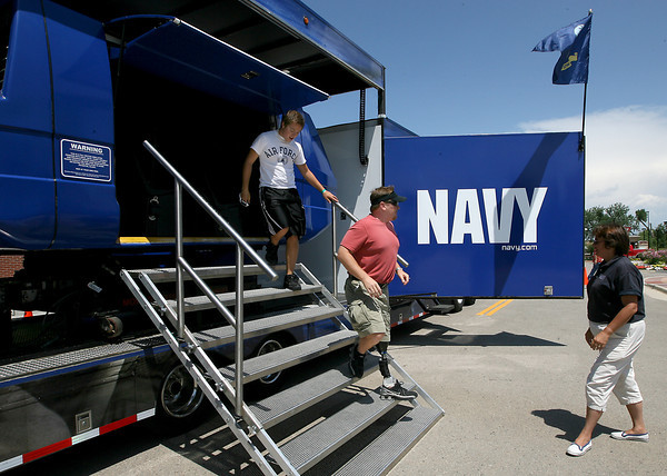 Robin Klotz, right, lets Joe Johnson, center, and son A.J. Johnson, 16, from Windsor, out of a U.S. Navy flight simulator Friday at The Promenade Shops at Centerrra in Loveland. The simulator, that seats 12 and gives the riders a point-of-view experience of flying in a F-18 Blue Angel, travels around the country promoting Navy awareness.