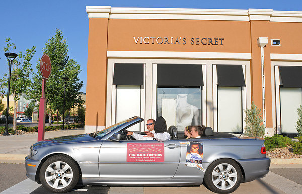"""Magician Jack Stephens drives a car while he is triple blindfolded on Thursday evening at the Promenade Shops with passengers Bob Snyder, who is running for Loveland City Council and his daughters Maria, 13, foreground in rear of car, and Sara, 11. The stunt was organized to promote the """"Masters of Magic"""" show on July 24 and 25 at the Rialto."""