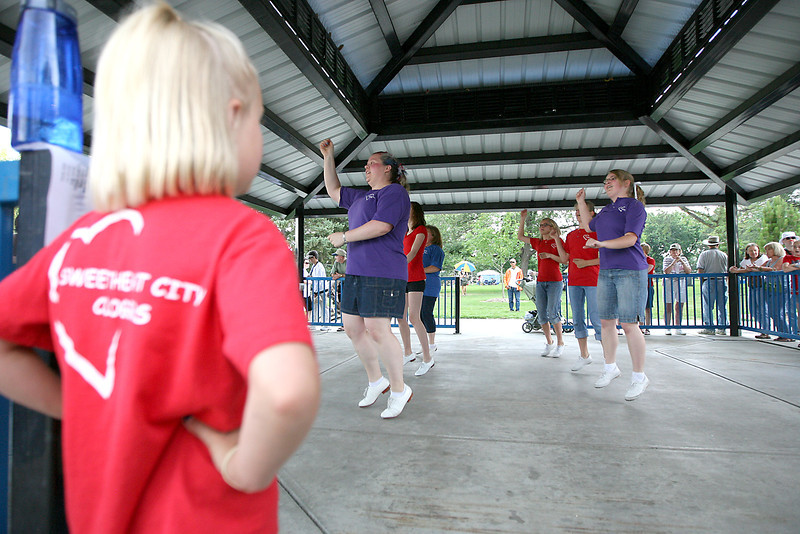 Susanna Lee, 7, looks on as other members of the Sweetheart City Cloggers, from left to right, Hilary Wade, Kadie Reid, Dale Littlefield, Lizzy Lee, Annie Lee, and Dionne Lee do a tap performance Saturday at North Lake Park.