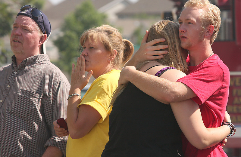 From left, Martin Gwin and Kaye Mason react while Amanda Mason is comforted by her cousin Nick Mason as they watch firefighters try to save their homes.