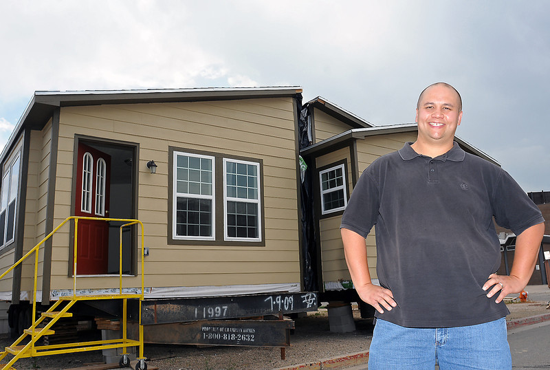 Loveland High School teacher Scott Burke poses Tuesday in front of a house that was built by students in his Geometry in Construction class last year.