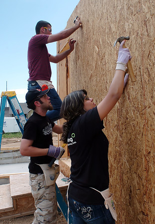 Iraqi college students Ava, 19, front, Fuad, 20, and Muhammad, 21, nail sheets of pressboard onto a house being built for Habitat for Humanity in Loveland, Colo. while volunteering Saturday with others in the World Learning program on July 17, 2010.