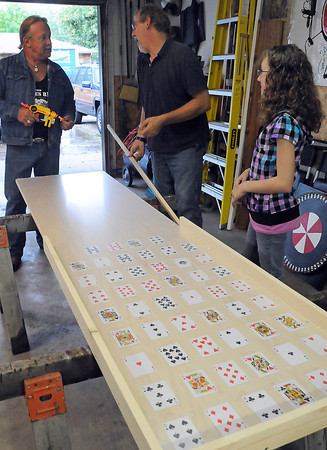 Charlie Knight, left, chats with Jon Thiede while Katie Thiede, 12, looks on Wednesday evening as Jon works on a card game that will be used in the upcoming Katie's Ride poker run and auction on July 18.