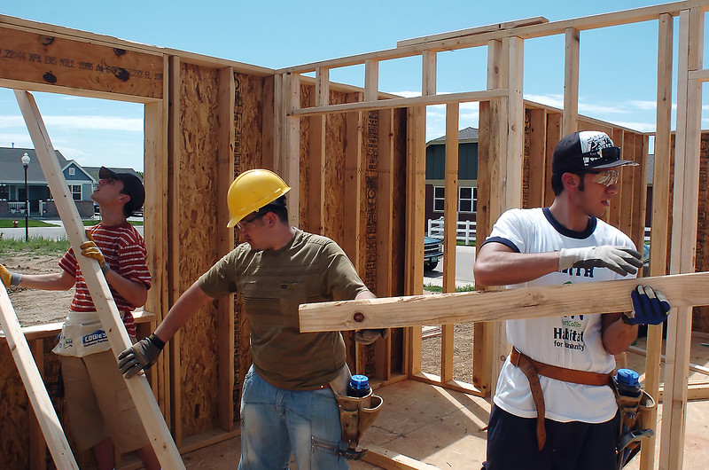Iraqi college students Haider, 20, left, Mohammed, 21, and Hassan, 21, pass boards into a house being built for Habitat for Humanity in Loveland, Colo. while volunteering with other students in the World Learning program on July 17, 2010.