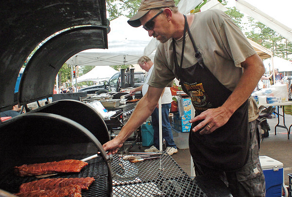 Rib-It co-owner Mark Lenz of Florence, Colo. cooks some ribs Saturday at the his booth during Loveland Loves Barbecue in downtown Loveland.