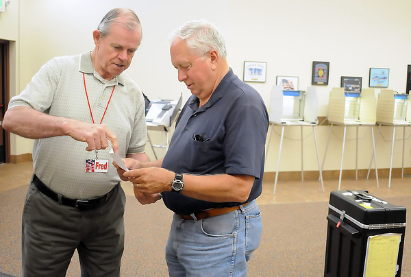 Election judge Fred Sugden, left, assists Loveland resident Ralph Wienbroeer as he prepares to drop off his ballot Wednesday afternoon at the Loveland Vote Service Center in the Police and Courts Building.