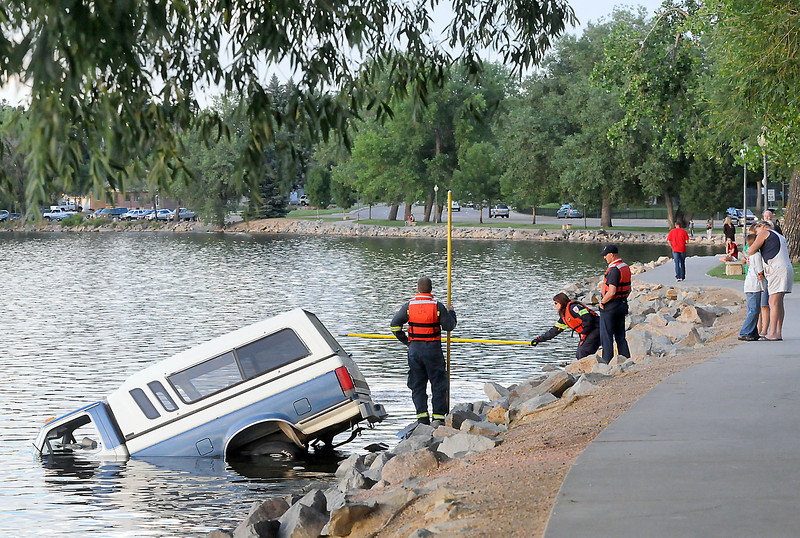 A pickup truck that crashed into Lake Loveland Wednesday evening rests in the water near South Shore Scenic Park as emergency personnel retrieve floating debris.