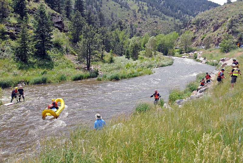 Members of Loveland Fire and Rescue's dive rescue team work together to assist a fisherman back to shore who became stranded by fast rushing water in the Big Thompson River while wading Friday afternoon.