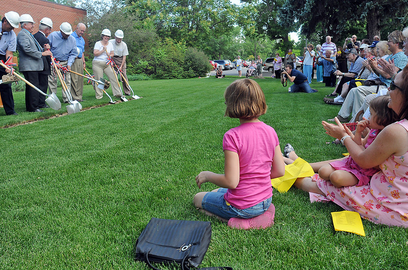 Renata Comeau, 9, center, sits on the lawn outside the Loveland Public Library with her little sister, Charlotte, 4, and mother, Elisabeth, as they watch the groundbreaking ceremony Thursday for the library's expansion and renovation project.