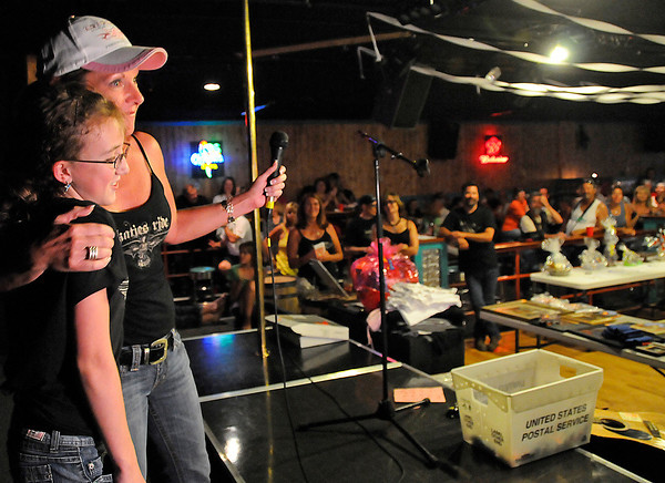 Kris Boone, wearing a hat, hugs Katie Thiede, 12 , after she sang to the crowd gathered at Crazy Jack's to raise money for Cystic Fibrosis during the Katie's Ride fundraiser in Fort Collins on Sunday.Riders started out with a poker run in the morning then an auction after lunch. All of the proceeds from Sunday will be sent to the Denver chapter of the Cystic Fibrosis Foundation.