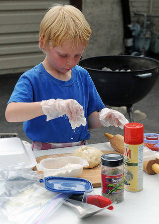 Seven-year-old Evan Beard of Thornton prepares a grilled pepperoni pizza Friday while competing in the Loveland Loves Barbecue Kids Q on Friday in downtown Loveland.