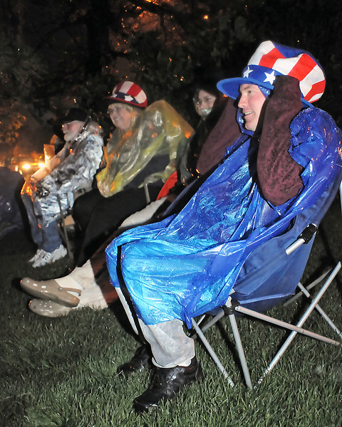 New Orleans resident Matthew Carpenter, right, tries to keep dry as he sits in the rain at South Shore Scenic Park on the south side of Lake Loveland waiting for the fireworks show to begin with, from left, Chuck and Margaret Thornburg of Loveland and Brian Lister, also of New Orleans. The Loveland fireworks show was postponed until 9:17 p.m. tonight at the same location over Lake Loveland.