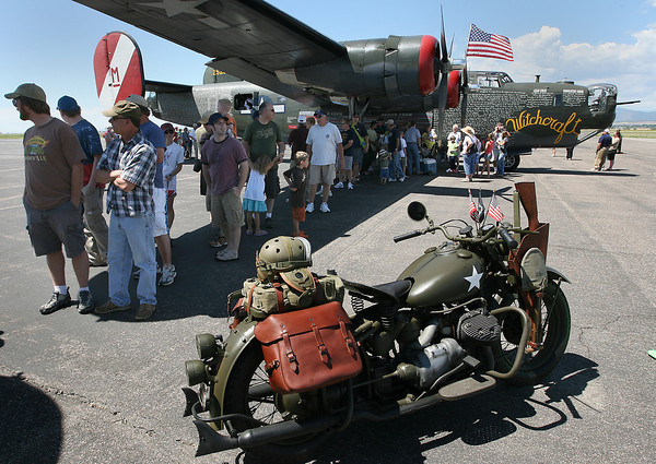 People stand in the shade of a B-24 Bomber and wait to tour a B-17 during the Wings of Freedom Tour on Sunday at the Loveland Airport.