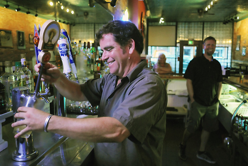Bob Gleason, left, pours a glass of beer Thursday evening while working at Chillers, 128 E. 4th St. in downtown Loveland with the bar's owner, Jeff Boulton, right.