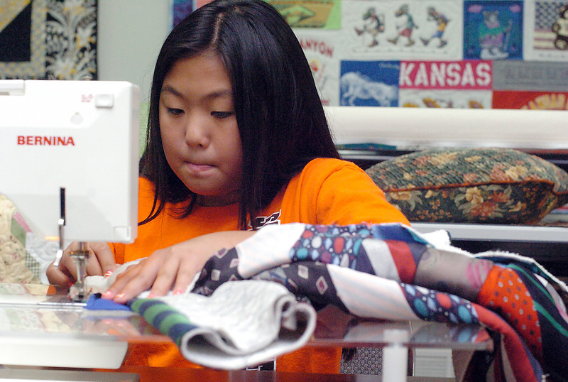 Ten-year-old Mia Roberts of Berthoud works on a jacket Wednesday at Sweetheart Quilt Shoppe in Loveland that she will be entering as a 4H recycled clothing project during the Larimer County Fair. Mia made the jacket using a variety of mens ties that she sewed onto a sweatshirt.