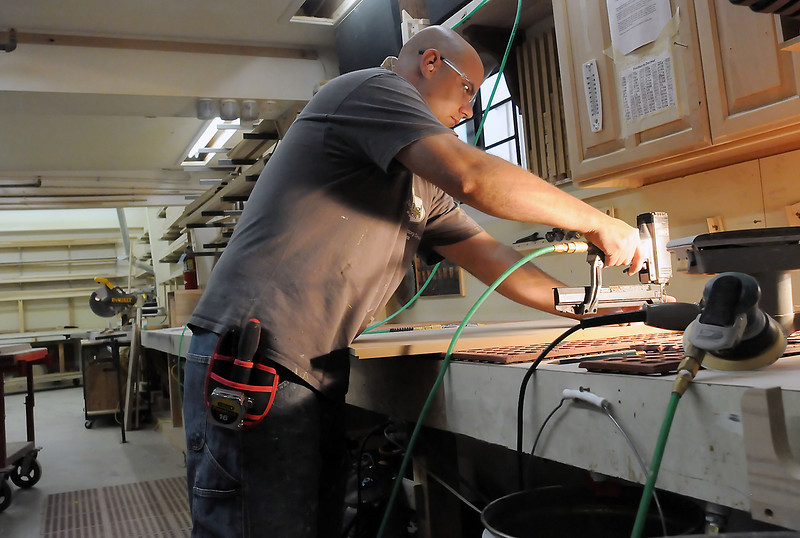 Jeremy Bustad works on a wood interior Thursday at one of the workstations at Tharp Cabinet Corp., 1246 Denver Ave., in Loveland.