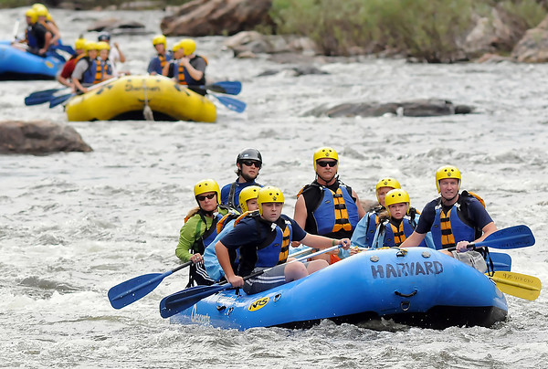 A line of rafts from Mountain Whitewater Descents floats down the Poudre River northwest of Fort Collins on Wednesday, July 21, 2010 with groups of paddlers.