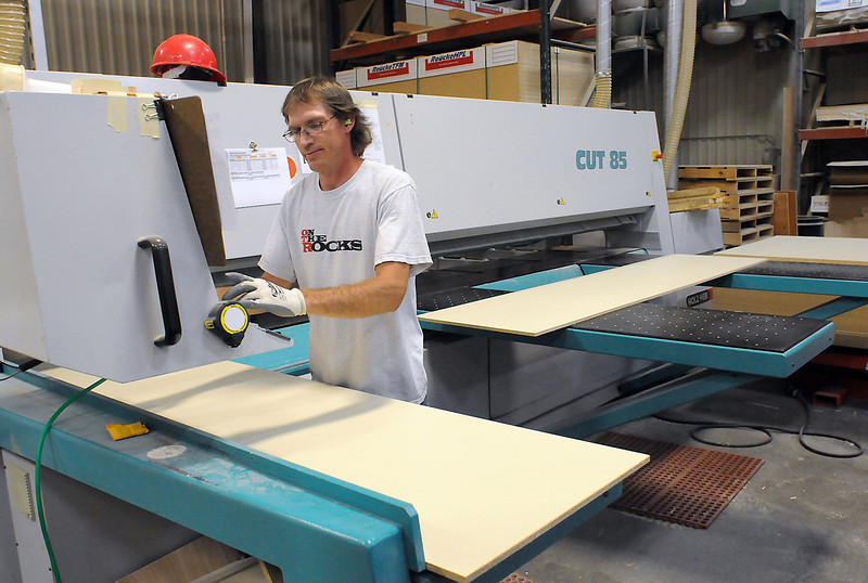 Mike Templeton uses a beam saw to cut wood components for a cabinet Thursday at Tharp Cabinet Corp., 1246 Denver Ave., in Loveland.